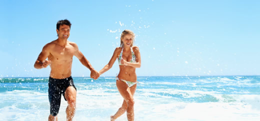Image of a happy couple running on beach