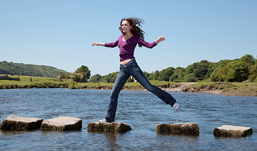 Image of woman on stepping stones across water