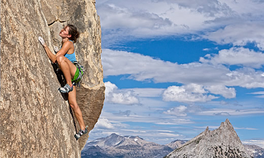 Image of a woman rock climber very high up a mountain