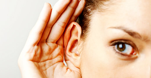 Woman cupping her hand over her ear assist listening