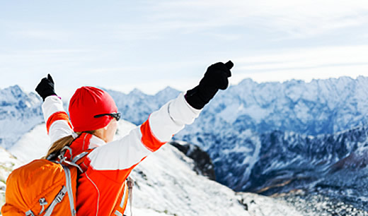 Triumphant woman at top of snowy mountain