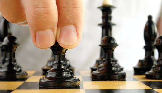 Man with fingers poised on a chess piece