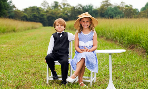 Boy and girl in Sunday Best outfits seated outdoors