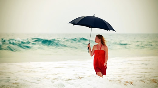 Young woman on the beach in heavy rain