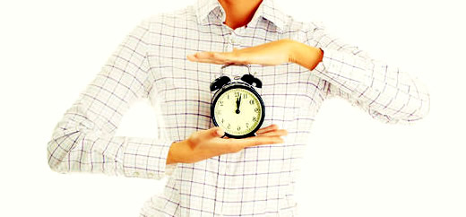 Woman holding an alarm clock between her palms